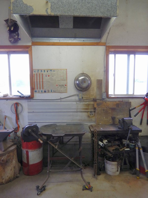 Welding area including anvil, forge, steel welding bench with vice backed with fireproof brick against steel siding on wall and spark proof exhaust hood with lighting.